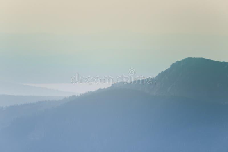 Un paysage rêveur et flou de montagnes près de coucher du soleil Flasre de Sun et regard brumeux dans des tons bleus Paysage de m photo libre de droits
