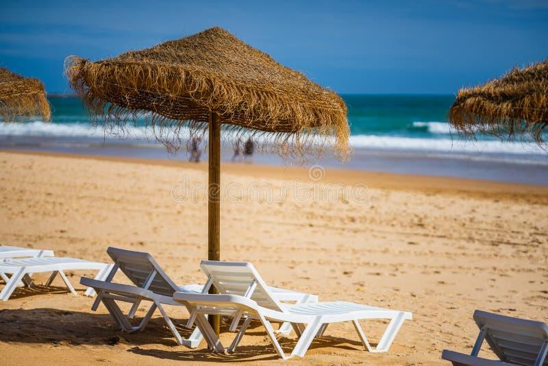 Un paysage renversant d'océan de mer avec des lits pliants et des parapluies dans Portimao, Portugal Région d'Algarve images stock