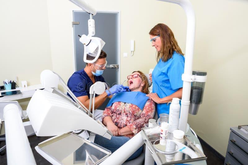 Un paziente che ottiene assistito e trattamento in uno studio dentario fotografie stock libere da diritti