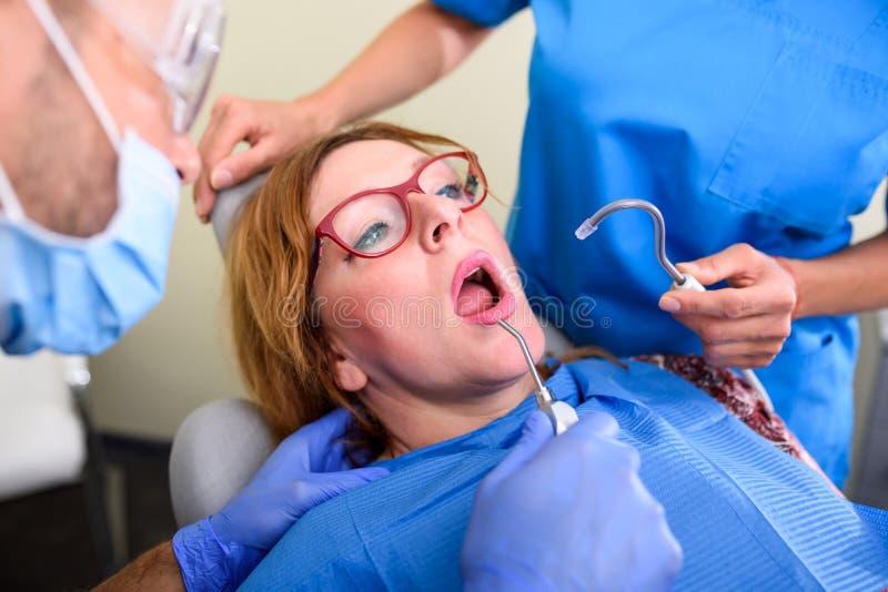 Un paziente che ottiene assistito e trattamento in uno studio dentario fotografie stock