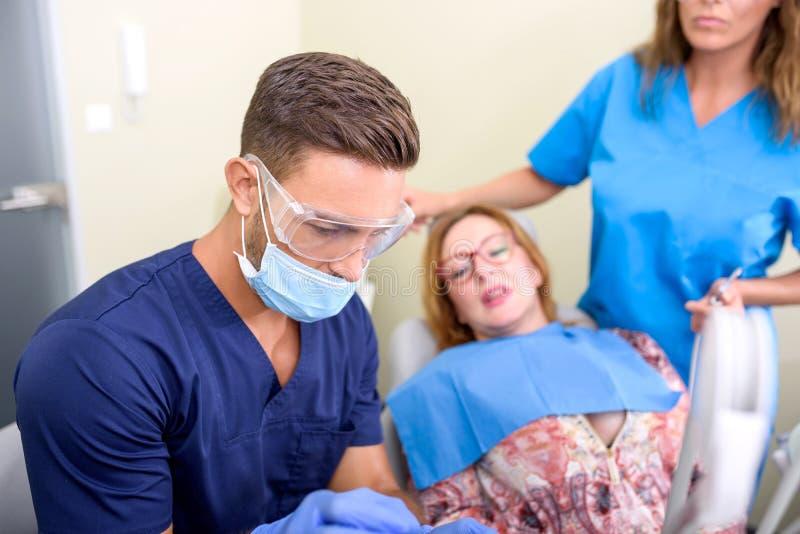 Un paziente che ottiene assistito e trattamento in uno studio dentario fotografia stock