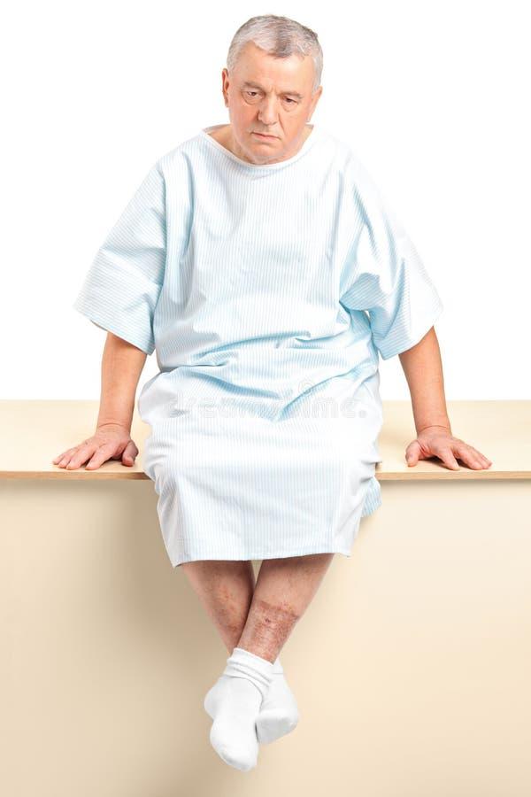 Un paziente maggiore preoccupato che si siede in un ospedale immagini stock