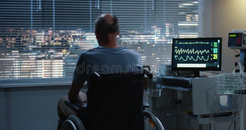 Un paziente in una sedia a rotelle tira su alla finestra fotografie stock