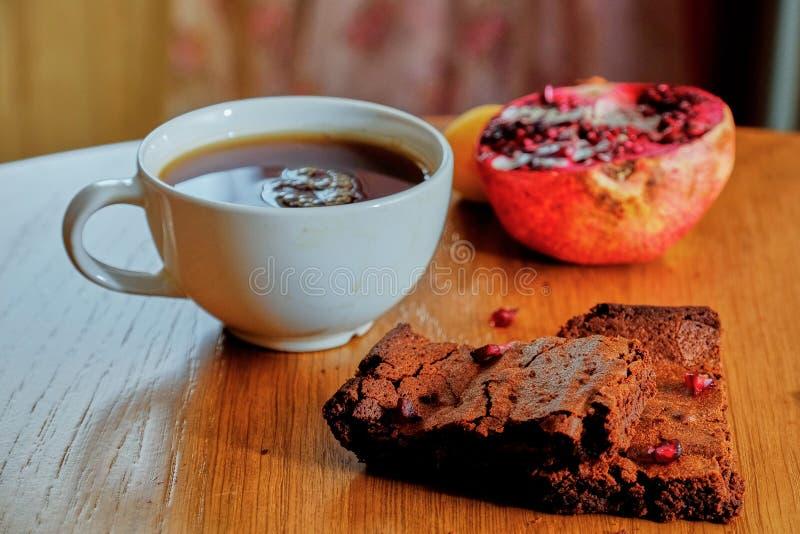 Un pedazo de brownie con una taza de café y de una granada en la tabla de madera fotografía de archivo