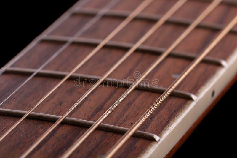 Un pedazo de fretboard con los trastes y las secuencias de una guitarra acústica foto de archivo
