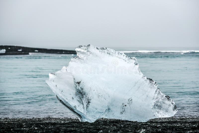 Un pedazo de iceberg que miente en la playa cerca de la isla azul de la laguna fotografía de archivo libre de regalías