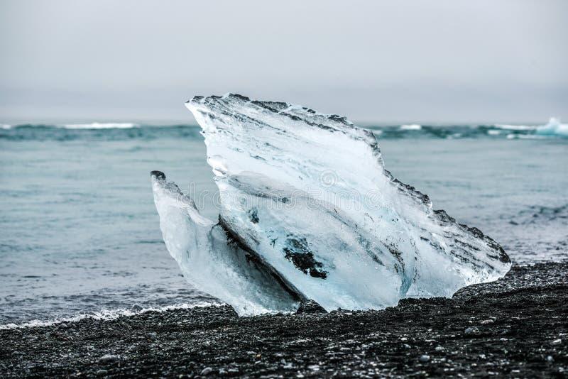 Un pedazo de iceberg que miente en la playa cerca de la isla azul de la laguna imágenes de archivo libres de regalías