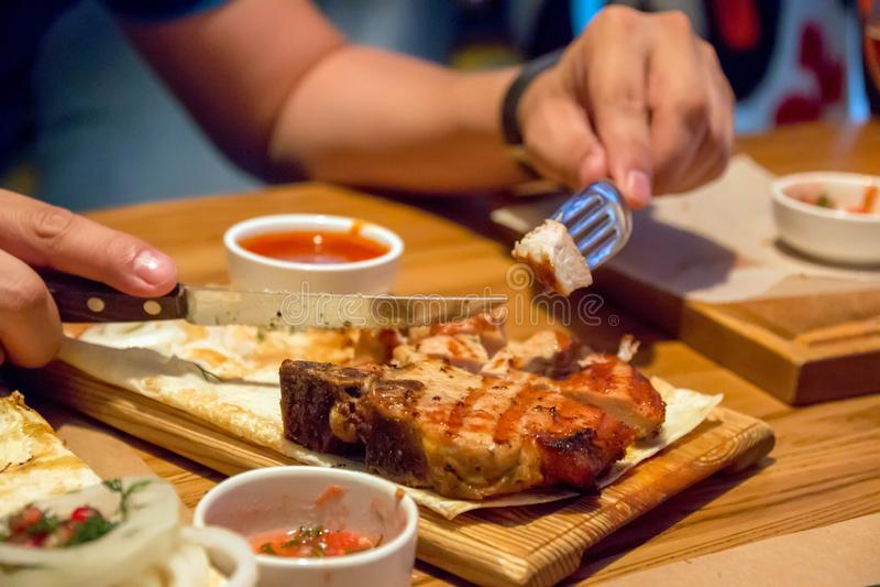 Un pedazo de kebab, en una placa de madera, las manos de los hombres sosteniendo una bifurcación y un cuchillo fotos de archivo