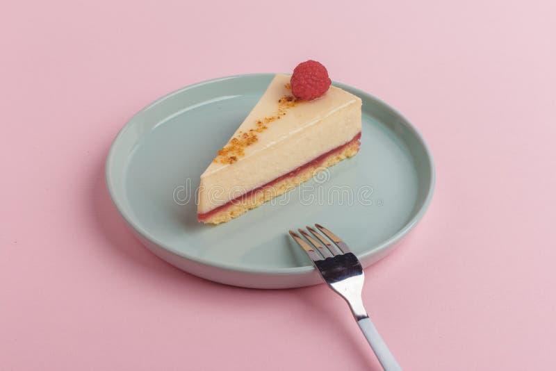 Un pedazo de la torta, pastel de queso en una placa con una bifurcación en un fondo rosado fotografía de archivo