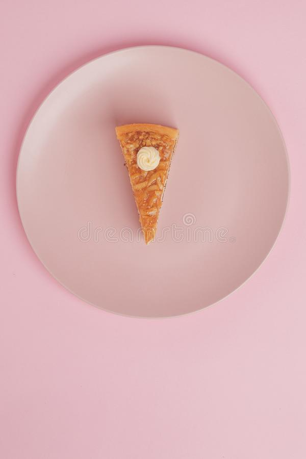 Un pedazo de la torta, pastel de queso en una placa con una bifurcación en un fondo rosado imagenes de archivo