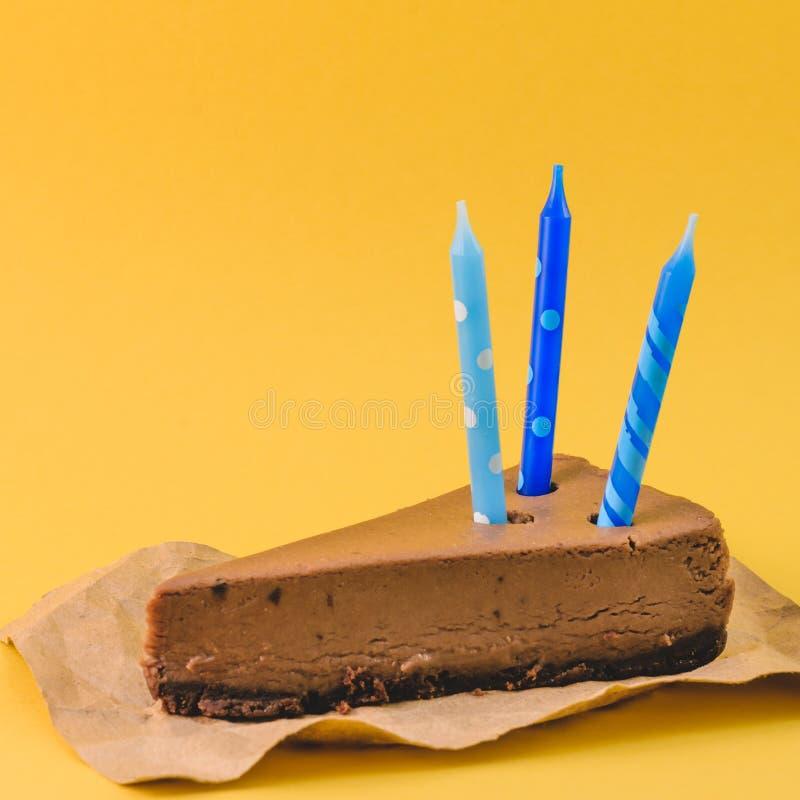 Un pedazo de pastel de queso del chocolate con la vela azul en un fondo amarillo imagenes de archivo