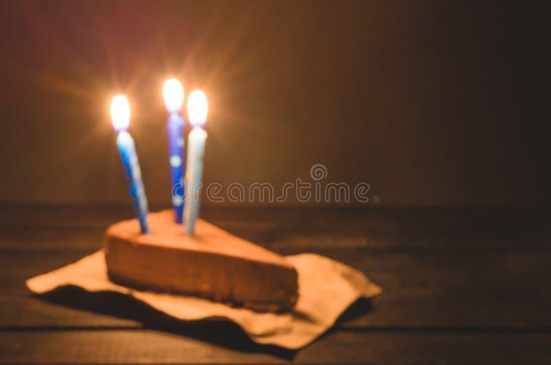 Un pedazo de pastel de queso del chocolate con la vela azul en un fondo amarillo imagen de archivo libre de regalías
