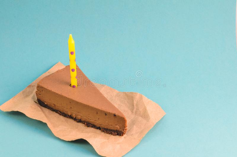 Un pedazo de pastel de queso del chocolate con una vela amarilla en un fondo azul fotografía de archivo