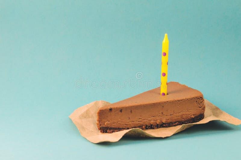 Un pedazo de pastel de queso del chocolate con una vela amarilla en un fondo azul imagen de archivo libre de regalías