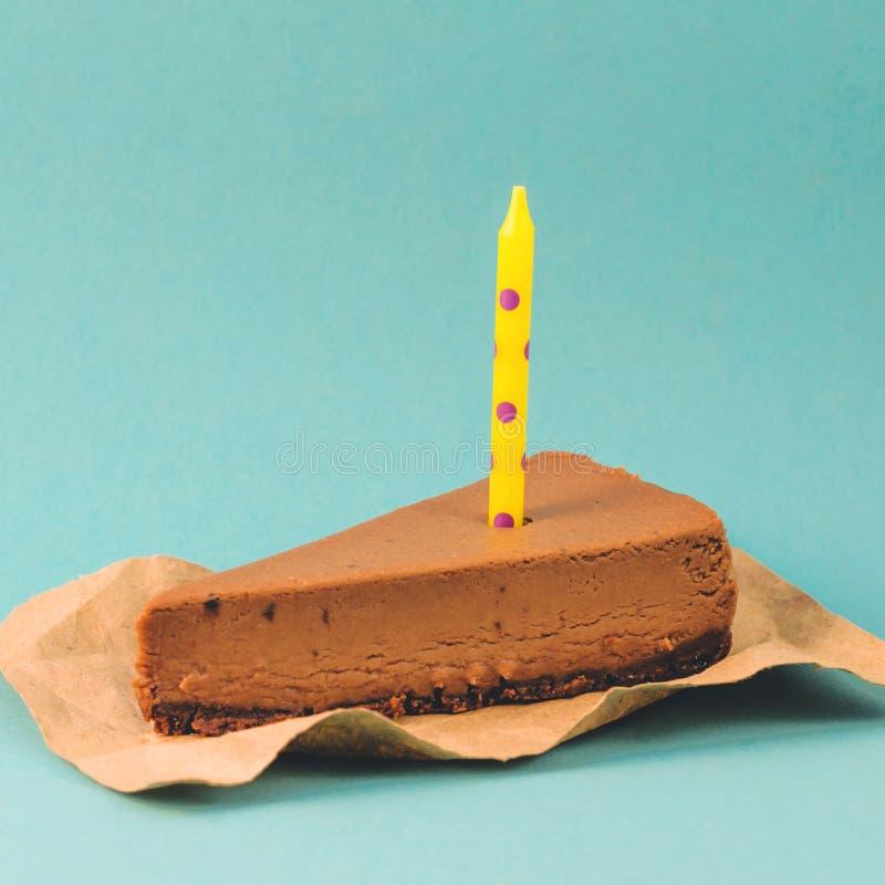 Un pedazo de pastel de queso del chocolate con una vela amarilla en un fondo azul foto de archivo
