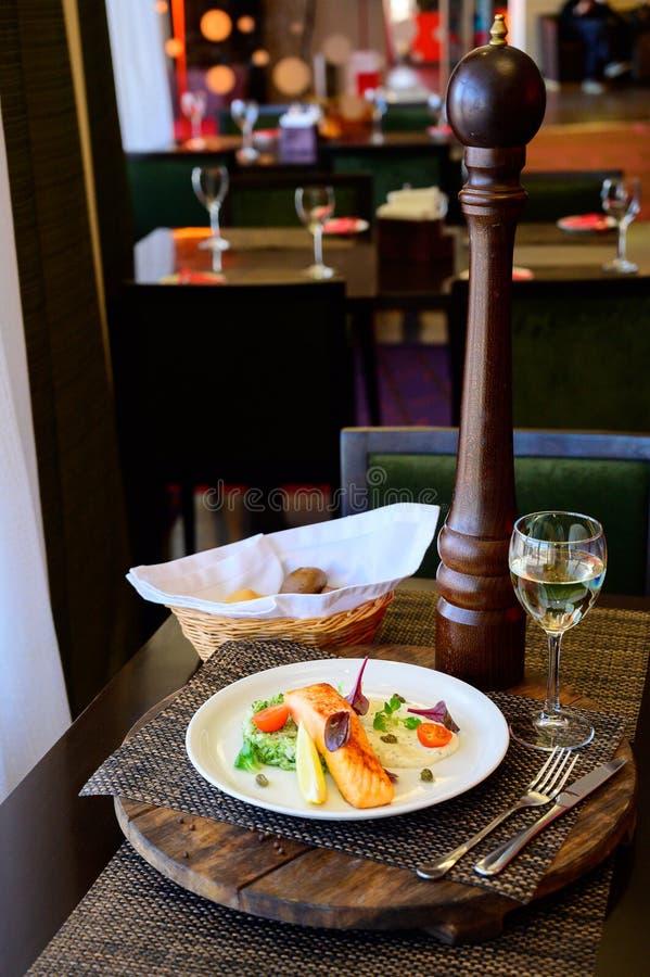 Un pedazo de pescados cocidos con el limón, las verduras y la salsa fotos de archivo