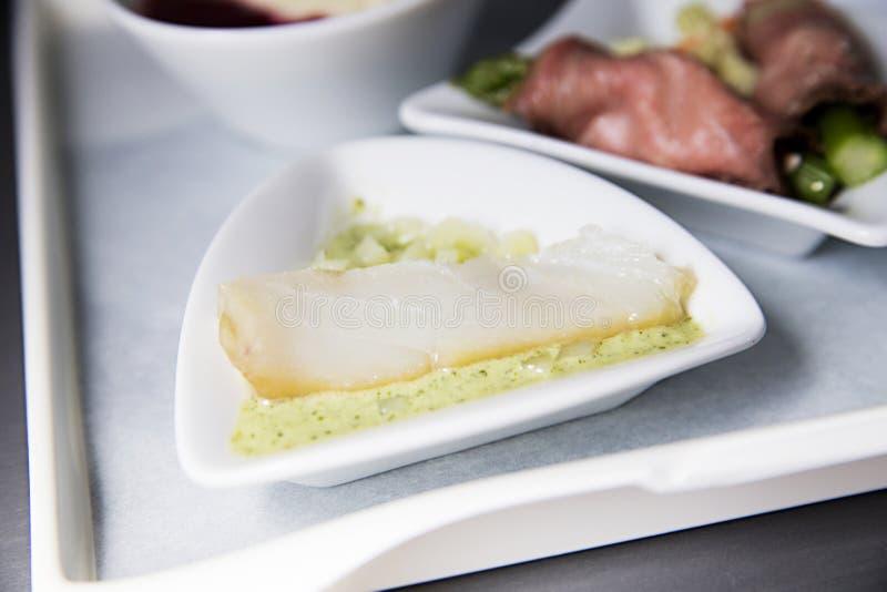 Un pedazo de pescados en una salsa le gusta un bocado en el avión foto de archivo libre de regalías