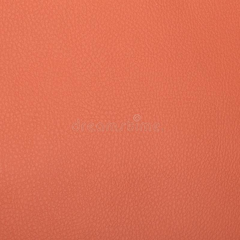 Un pedazo de primer rosado-anaranjado de la textura del cuero artificial foto de archivo