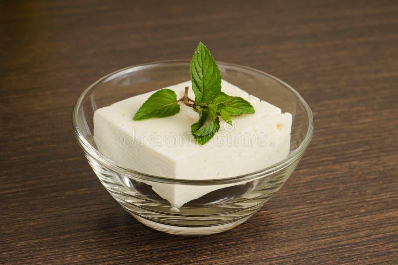 Un pedazo de queso blanco en bol de vidrio foto de archivo