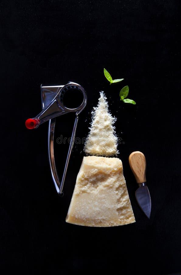 Un pedazo de queso parmesano en oscuridad con un rallador manual a del queso foto de archivo