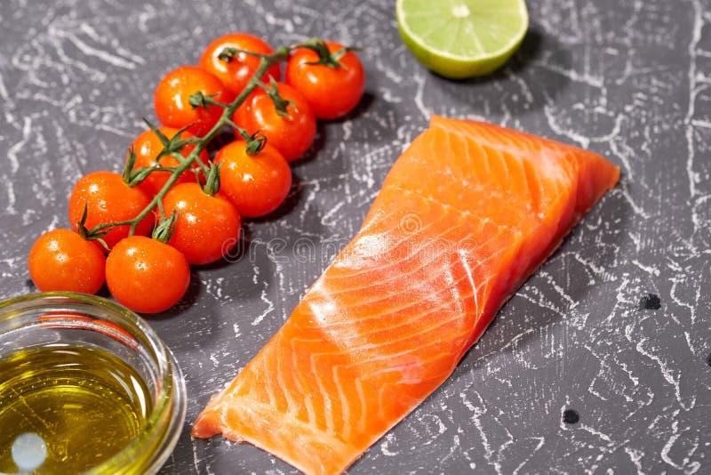 Un pedazo de salmones en un fondo gris, tomates, eneldo, aceite de oliva, limón Foco selectivo, espacio para el texto fotografía de archivo libre de regalías