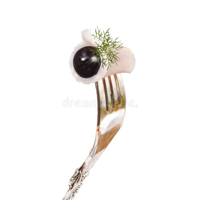 Un pedazo de tocino salado con la aceituna y el eneldo fijados en una bifurcación foto de archivo libre de regalías