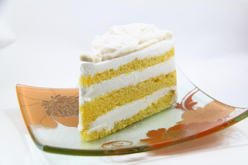 Un pedazo de torta de coco en el fondo blanco imagenes de archivo