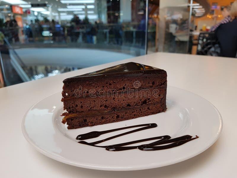 Un pedazo de torta en una placa blanca en una tabla blanca, un café en el fondo imágenes de archivo libres de regalías