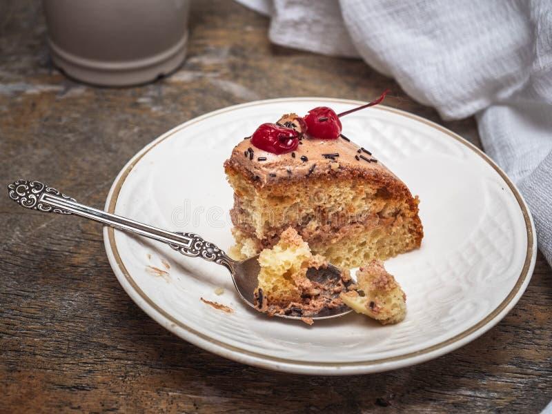 Un pedazo de torta hecha en casa, que comenzó a comer Torta en un platillo y una cucharilla blancos del vintage imagen de archivo