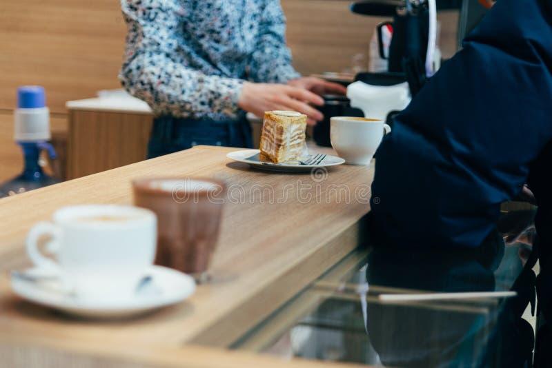 un pedazo de torta y un cubilete blanco se traslapan en un contador en un café, camarero, camarero foto de archivo libre de regalías