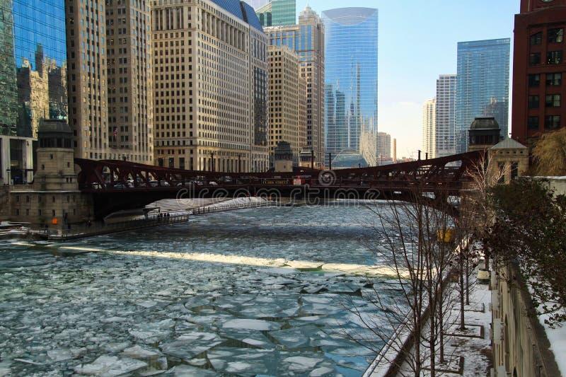 Un pedazo del hielo cubierto, el río Chicago congelado es aguamarina azul y corre a través del lazo de Chicago imagen de archivo