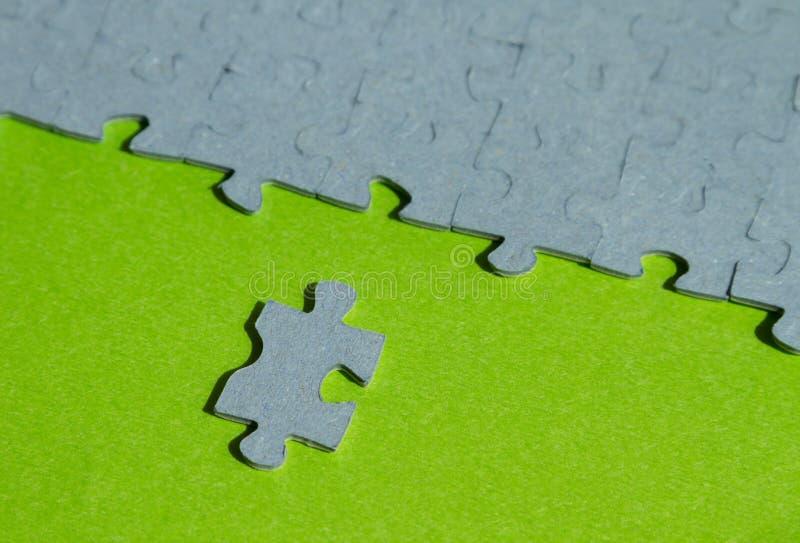 Un pedazo del rompecabezas cortado en fondo verde foto de archivo