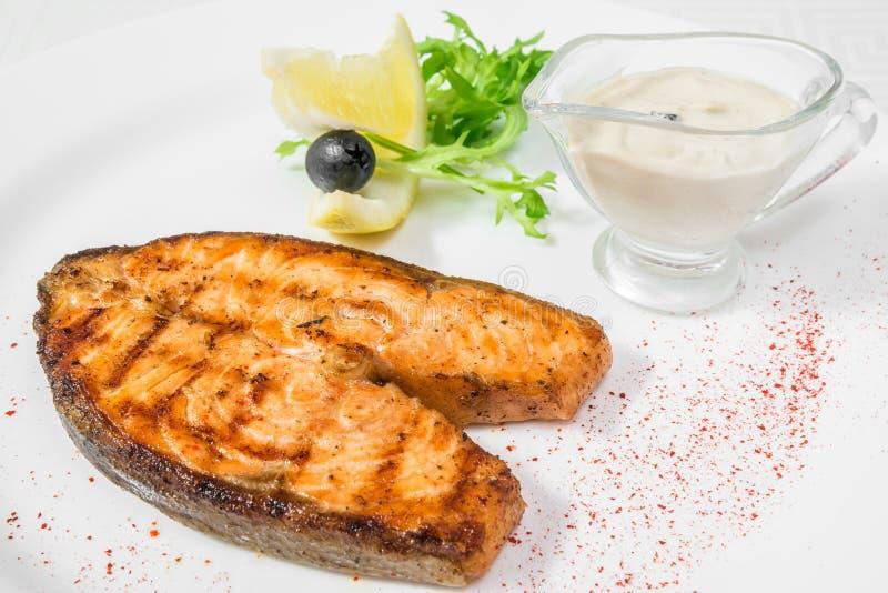 Un pedazo grande delicioso de pescados fritos con la salsa, el limón y las hierbas Marco horizontal imagenes de archivo