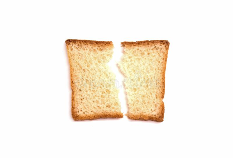 Un pedazo quebrado de mentiras de la tostada del pan blanco en un fondo blanco foto de archivo