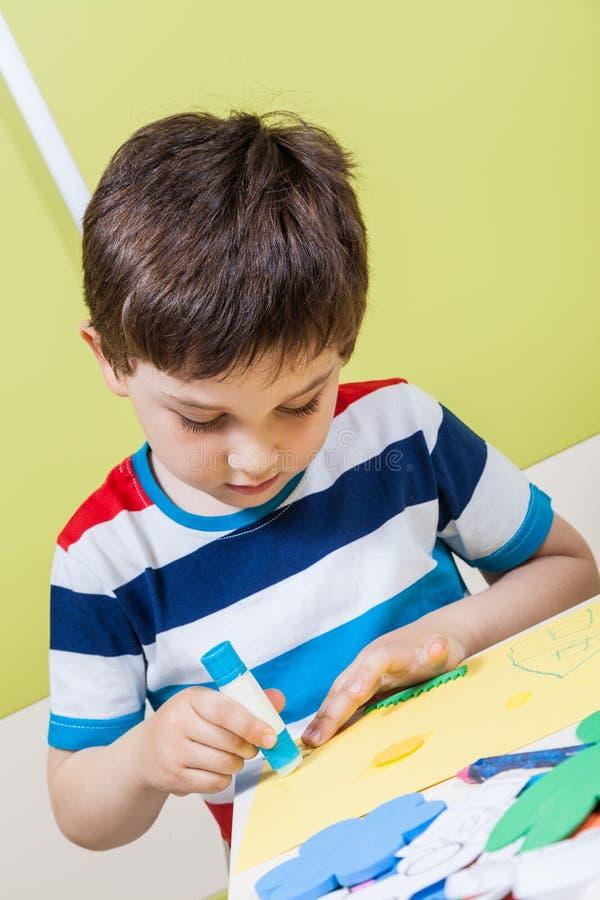 Un pegamento preescolar del uso del muchacho para la preparación fotografía de archivo libre de regalías