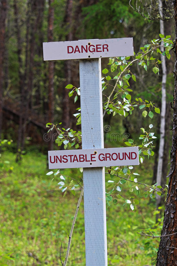 Un peligro, muestra de tierra inestable a lo largo de una pista de senderismo fotografía de archivo libre de regalías