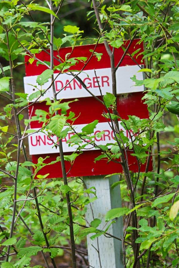 Un peligro, muestra de tierra inestable obscurecida por los árboles imagen de archivo