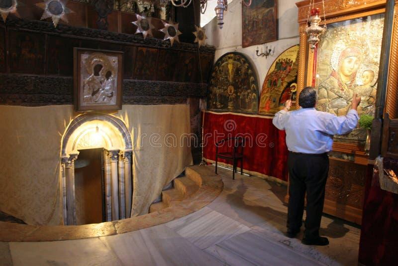 Un pellegrino prega davanti alle immagini del vergine con il bambino Gesù, vicino all'entrata alla caverna della nascita del ` di immagini stock