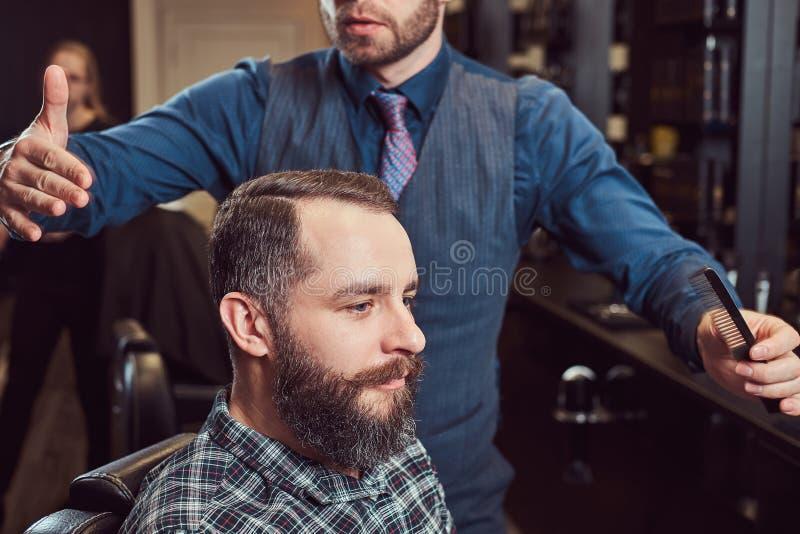 Un peluquero principal elegante hace un corte de pelo al cliente Corte de pelo del ` s de los hombres en una barbería imagenes de archivo