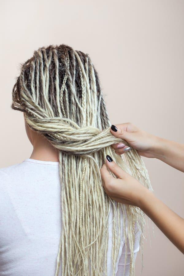 Un peluquero teje dreadlocks a una chica joven hermosa imagen de archivo libre de regalías