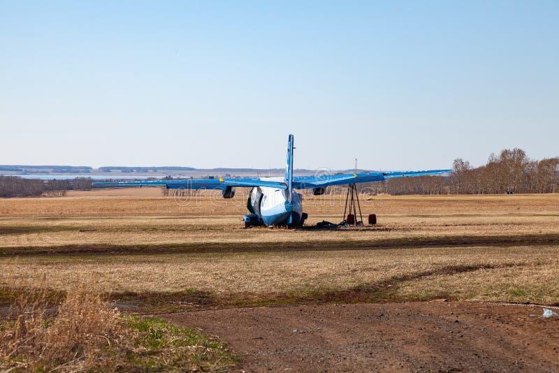 Un pequeño avión para el transporte de pasajeros y de paracaidistas está detrás de la cerca en un campo de la hierba amarilla en  fotos de archivo libres de regalías