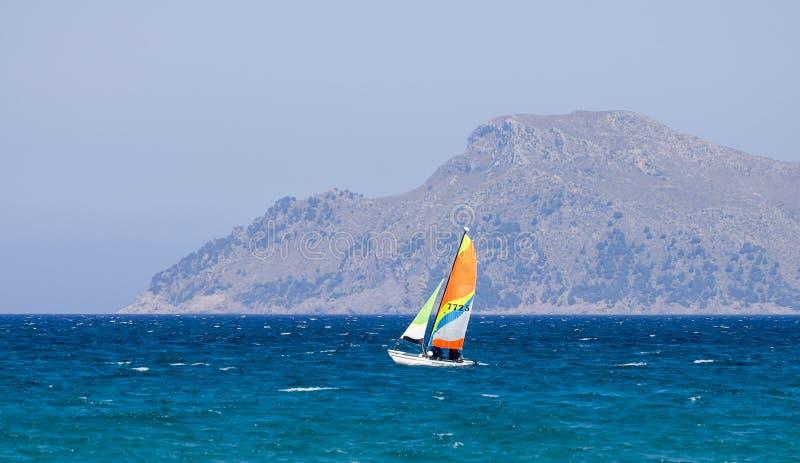 Un pequeño barco de navegación en la bahía de Alcudia cerca puede ciudad de Picafort, Majorca imagen de archivo