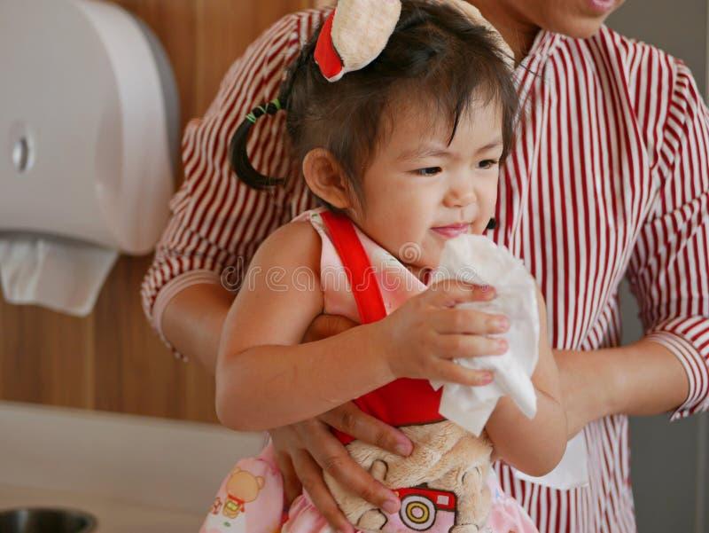 Un pequeño bebé asiático, con ayuda de su madre, aprendiendo limpiar sus manos después de lavarlas imagen de archivo