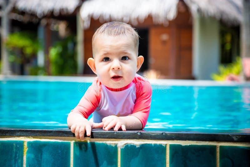 Un pequeño bebé lindo y feliz se sostiene al lado de la piscina tropical y a las miradas a la cámara con nadada de la niña pequeñ imagenes de archivo