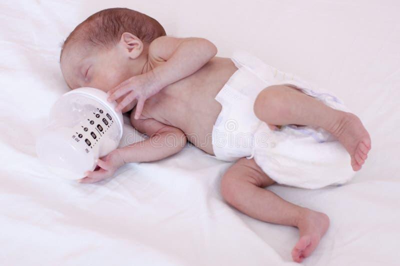 Un pequeño bebé prematuro que come una fórmula de la leche de una botella fotos de archivo