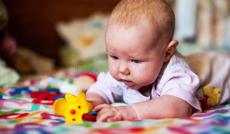 Un pequeño bebé que juega en una manta foto de archivo