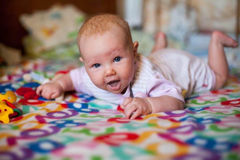 Un pequeño bebé que juega en una manta fotos de archivo