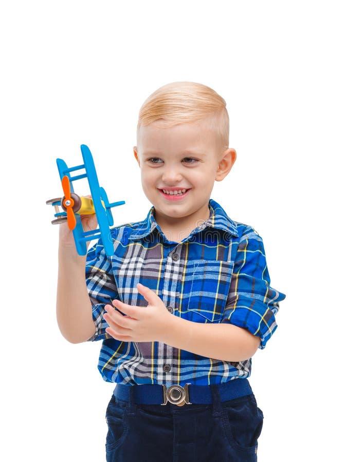 Un pequeño bebé que se divierte que juega con un aeroplano del juguete y que sonríe feliz Aislado en blanco imágenes de archivo libres de regalías