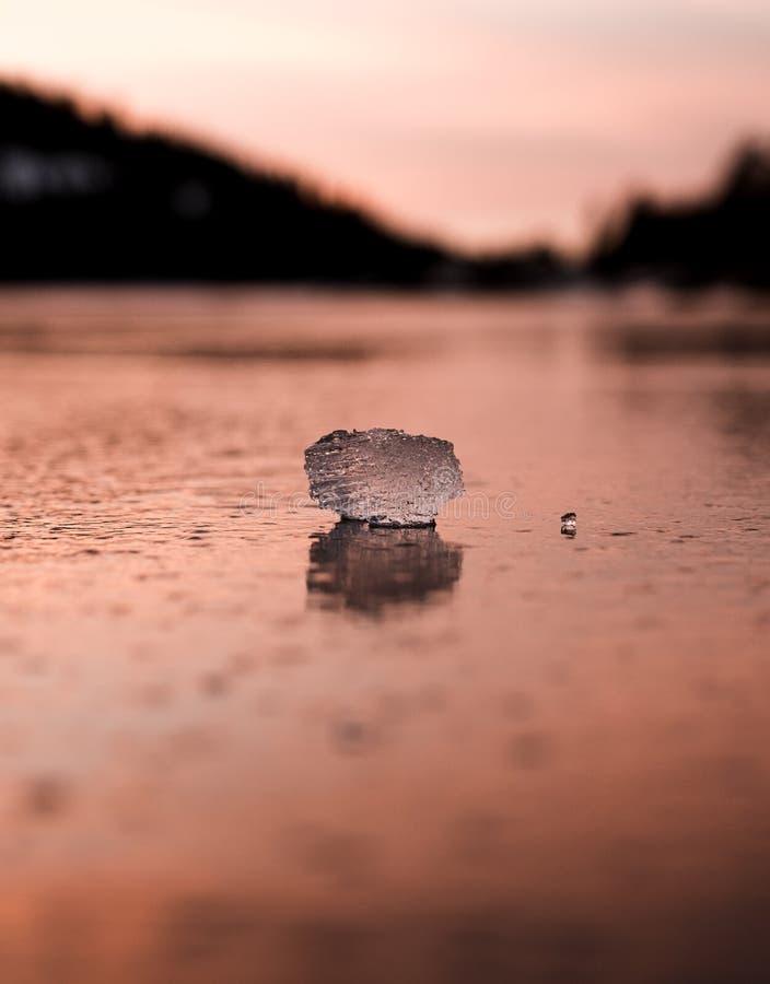 Un pequeño bloque de hielo es anaranjado en un lago congelado imagen de archivo libre de regalías