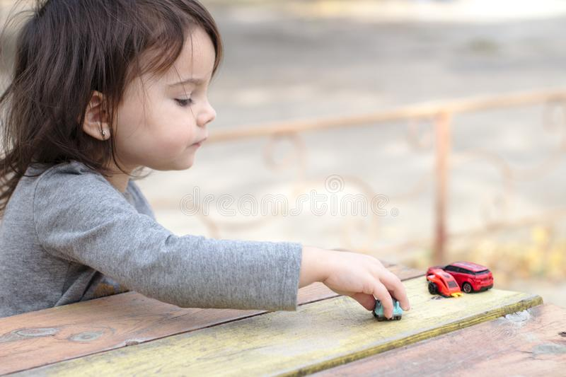 un pequeño children& x27; puntos de la mano de s a un coche del juguete entre una multitud de coches en una tabla rojo-amarilla d fotografía de archivo libre de regalías